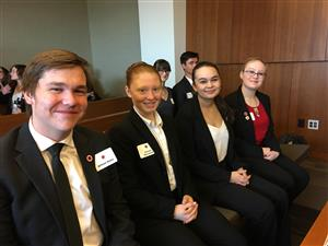 Four Mock Trial students sitting in the courtroom
