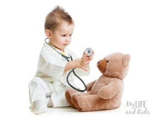 Toddler holding a stethoscope playing doctor with his brown stuffed teddy bear